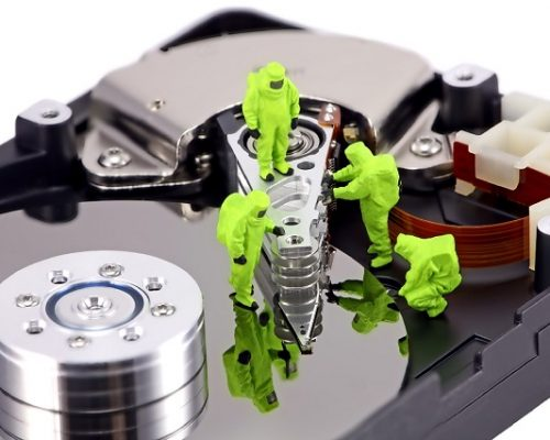 Concept image of a HAZMAT (Hazardous Materials) team closely inspecting a hard drive for viruses, spyware and trojans. Taken with a Canon 5D.